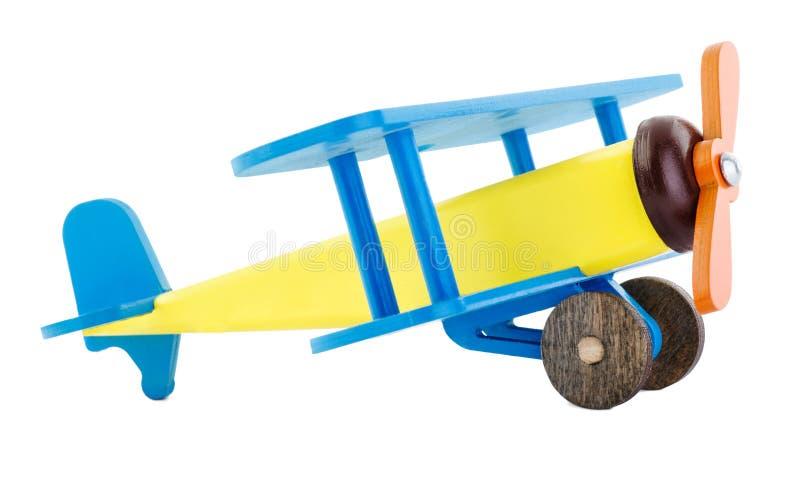 Un faux avion lumineux du ` s d'enfant fait de bois d'isolement sur le fond blanc Vue de côté images stock