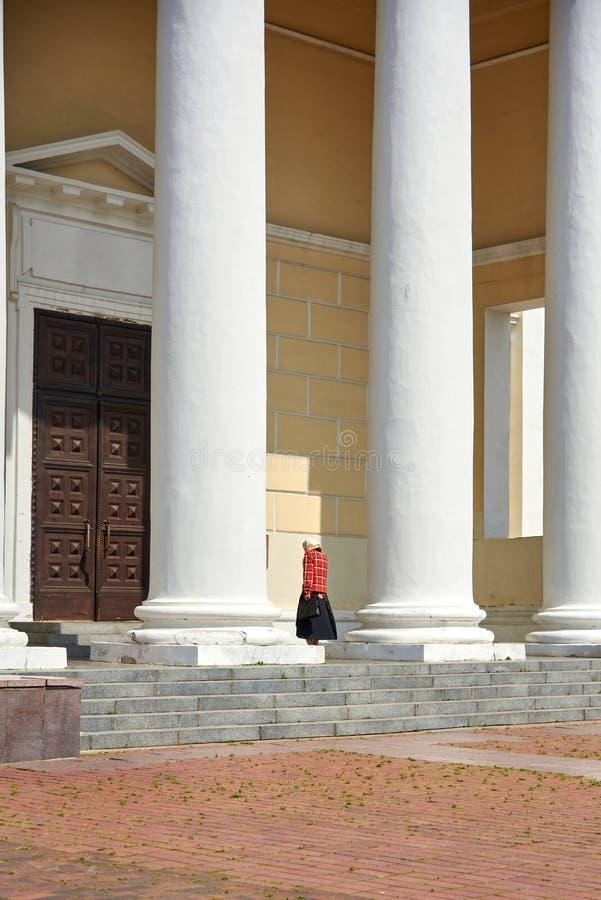 Un feligrés solo camina a la puerta de una iglesia ortodoxa, una estructura arquitectónica hermosa fotos de archivo