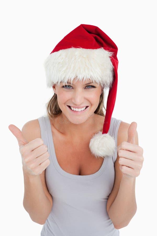 Un femme avec les pouces se lèvent et un chapeau de Noël photographie stock libre de droits