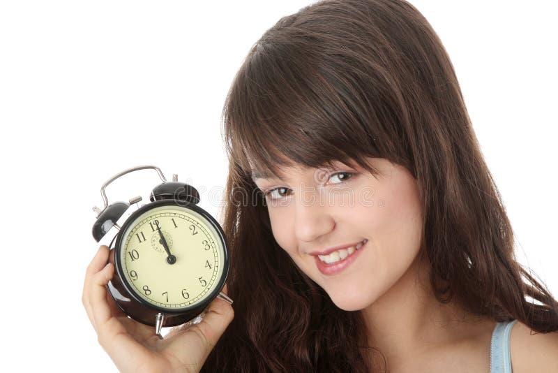 Un femme de l'adolescence avec l'horloge d'alarme image libre de droits