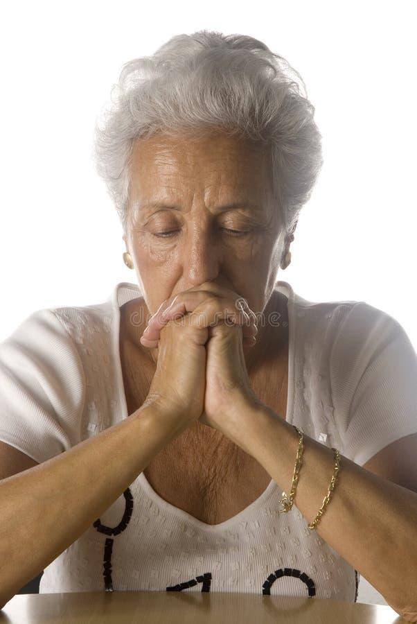 Un femme plus âgé dans la prière profonde photo libre de droits