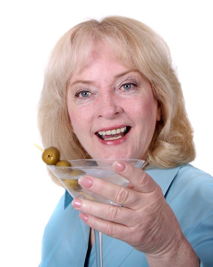 Un femme plus âgé retenant un martini photographie stock
