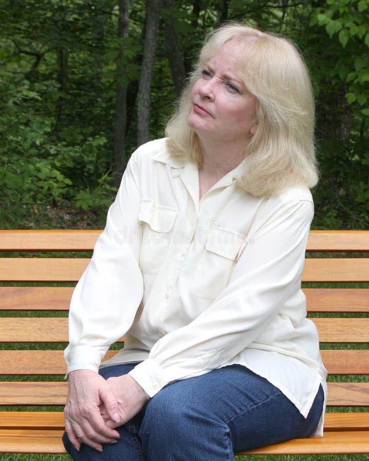 Un femme plus âgé s'asseyant sur un banc de stationnement photo stock