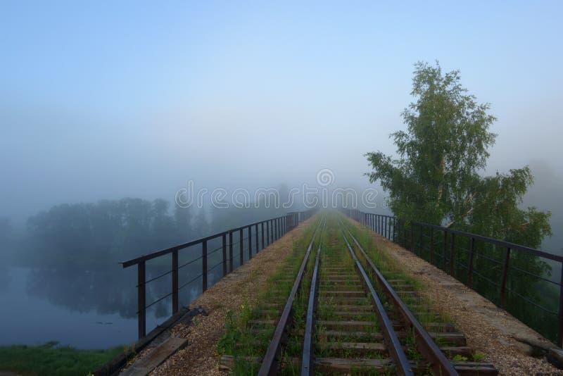 Un ferrocarril viejo que corre lejos a través del río a través de la niebla de la mañana imagenes de archivo