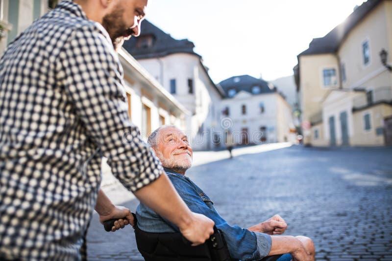 Un figlio adulto con il padre senior in sedia a rotelle su una passeggiata in città fotografia stock