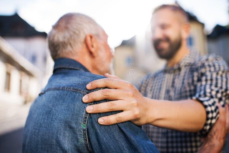 Un figlio adulto dei pantaloni a vita bassa con il padre senior su una passeggiata in città fotografia stock libera da diritti