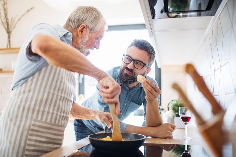 Un figlio adulto dei pantaloni a vita bassa e un padre senior all'interno a casa, cucinando immagini stock