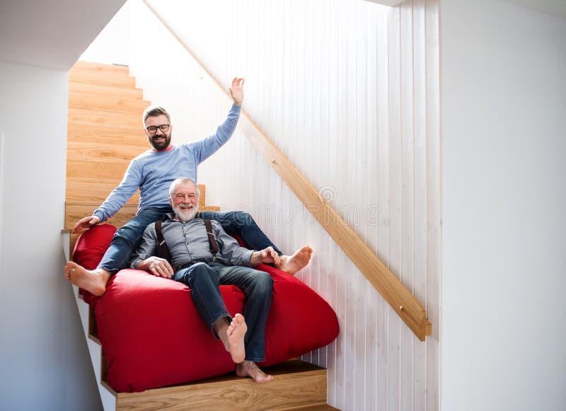 Un figlio adulto dei pantaloni a vita bassa e un padre senior all'interno a casa, divertendosi fotografia stock