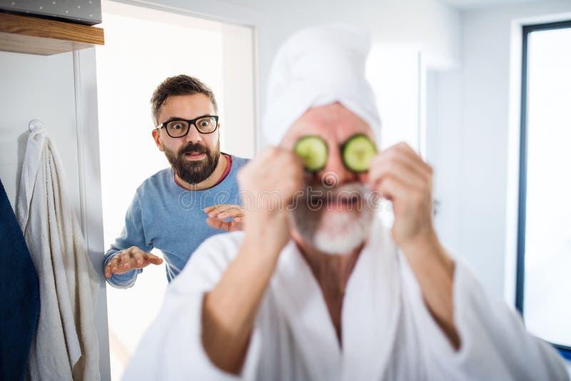 Un figlio adulto dei pantaloni a vita bassa e un padre senior in bagno all'interno a casa, divertendosi fotografie stock libere da diritti