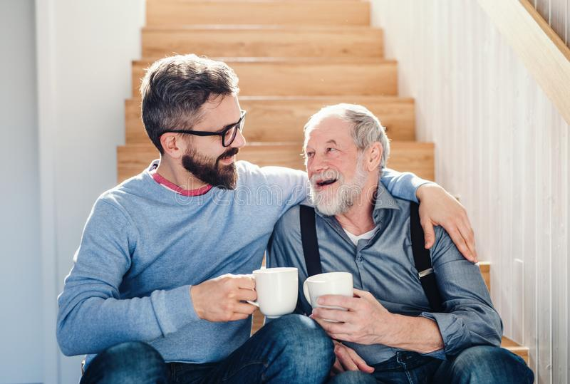 Un figlio adulto dei pantaloni a vita bassa e un padre senior che si siedono sulle scale all'interno a casa, parlando immagini stock libere da diritti