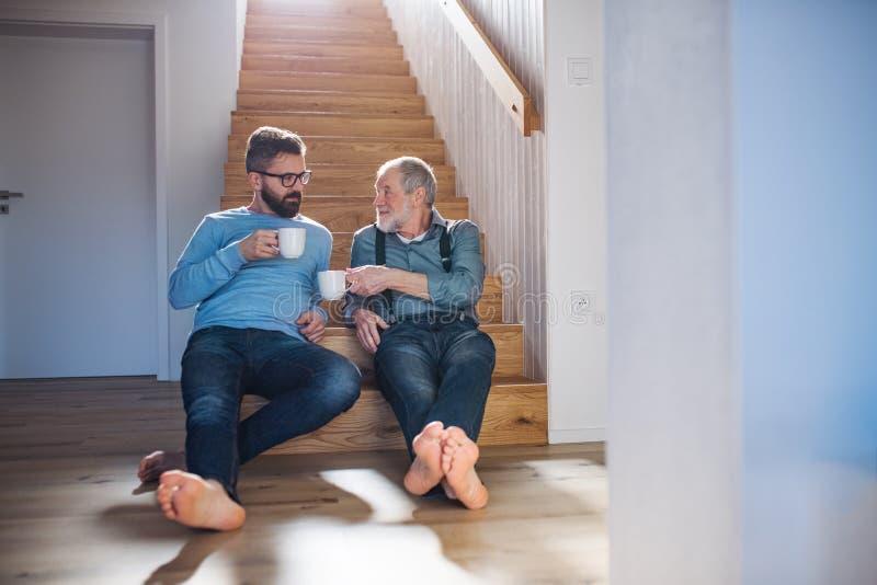Un figlio adulto dei pantaloni a vita bassa e un padre senior che si siedono sulle scale all'interno a casa, parlando fotografie stock libere da diritti
