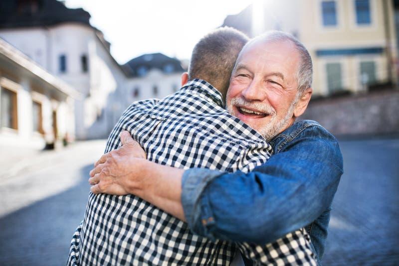 Un figlio adulto dei pantaloni a vita bassa ed suo padre senior in città, abbracciante fotografia stock libera da diritti