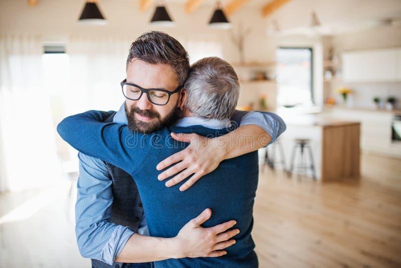 Un figlio adulto e un padre senior all'interno a casa, abbracciando immagini stock