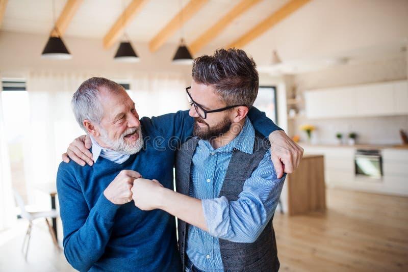 Un figlio adulto e un padre senior all'interno a casa, facendo l'urto del pugno fotografia stock libera da diritti