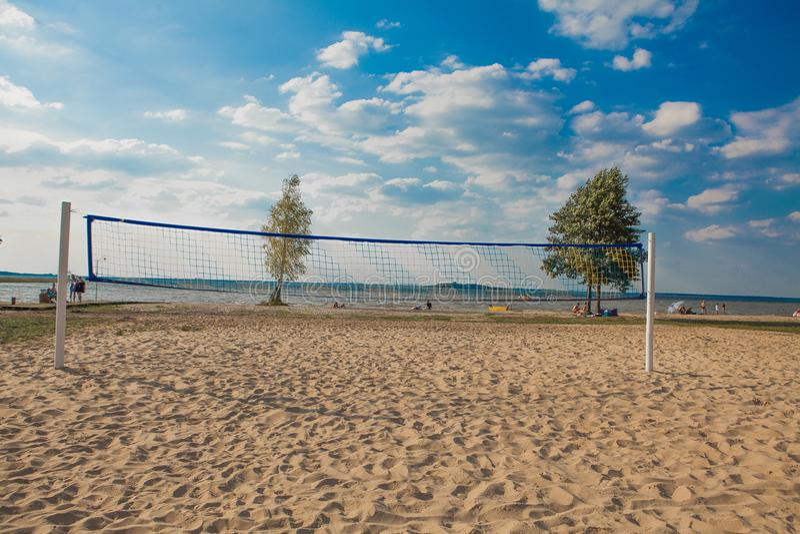 Un filet de volleyball de plage un beau jour ensoleillé Accomplissez la plage et la mer de sable image stock