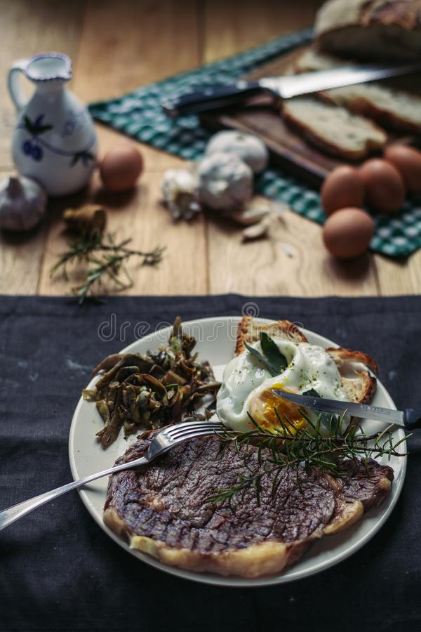 Un filete asado a la parrilla y un pedazo de pan cortaron con un cuchillo, los huevos, el romero, el aceite de oliva y el ajo imágenes de archivo libres de regalías