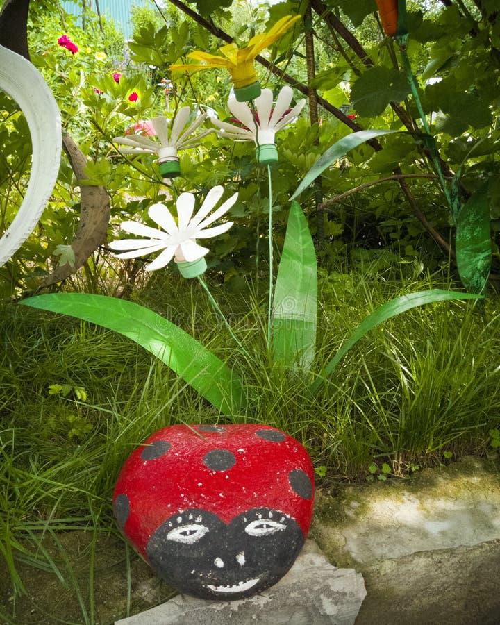 Un fiore da una bottiglia di plastica Coccinella fatta della pietra Decorazione per il fai-da-te del giardino Riutilizzi di plast fotografia stock libera da diritti