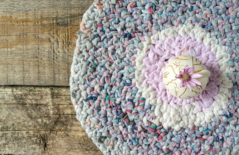 Un fiore lilla Xeranthemum sul vaso rotondo dell'argilla sulla toppa tricottata immagine stock libera da diritti