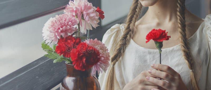Un fiore in mani del ` una s della ragazza fotografia stock libera da diritti