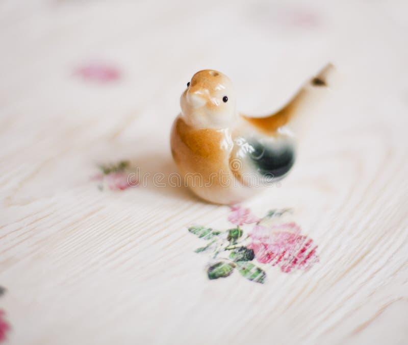 Un fischio è un usignolo dell'uccellino su un fondo, nello stile di un'eleganza misera fotografia stock