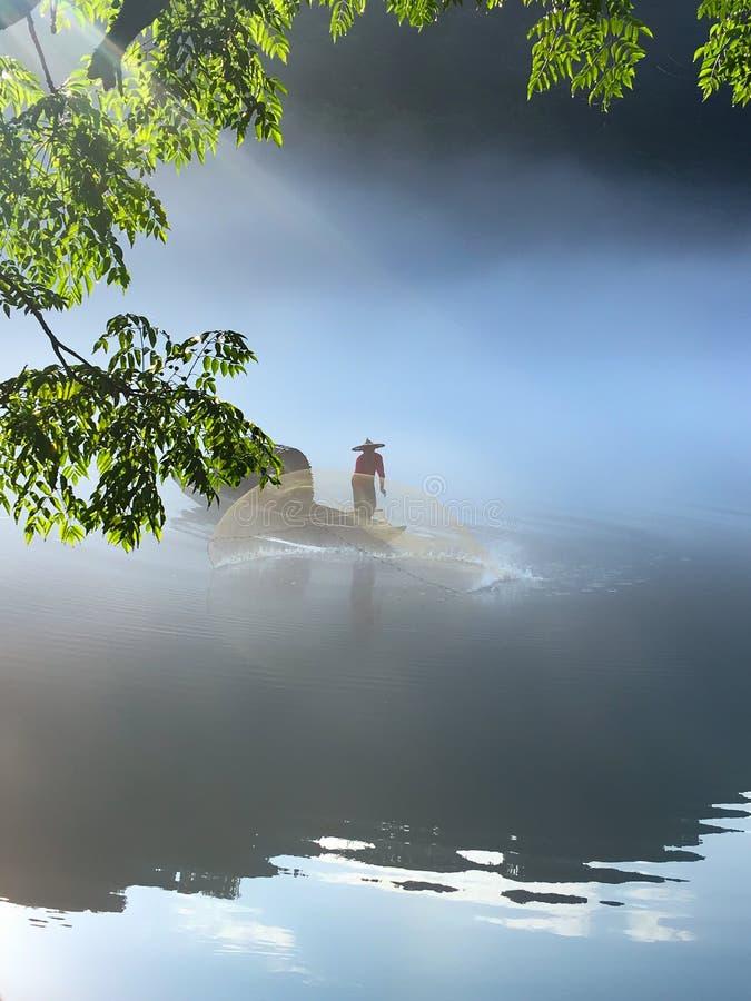 Un fishman ech? una red en la niebla en el r?o imagen de archivo