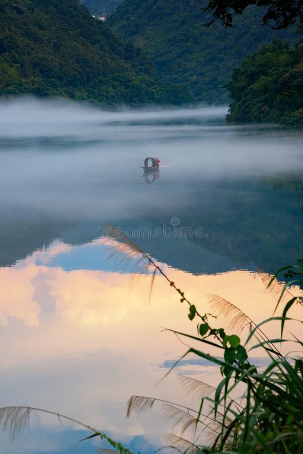 Un fishman en el barco en la niebla en el río, la reflexión de oro de la nube en la superficie del agua fotos de archivo libres de regalías