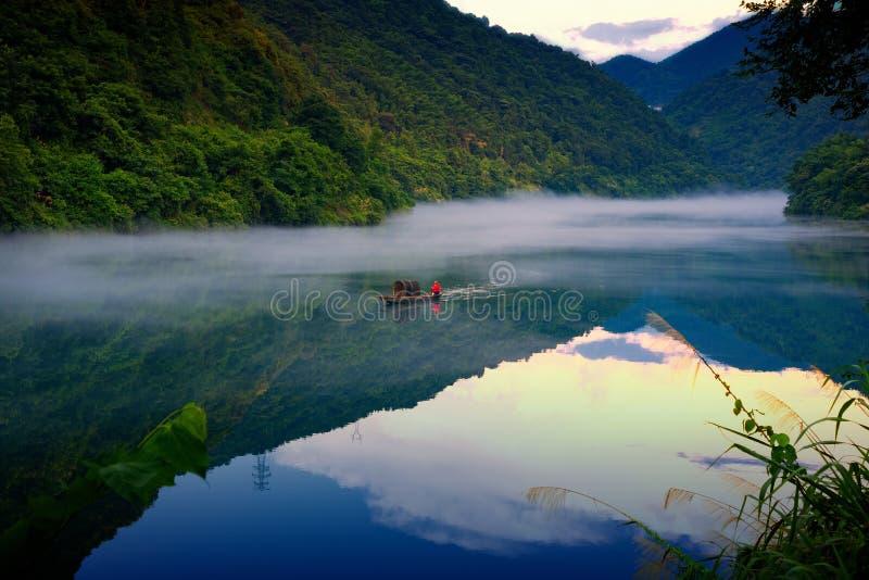 Un fishman sur le bateau dans le brouillard sur la rivière, la réflexion d'or de nuage sur la surface de l'eau photos libres de droits