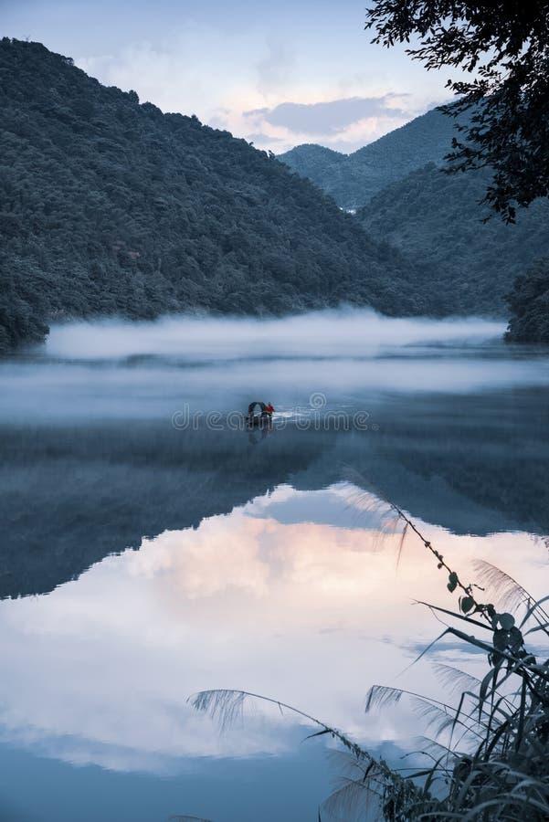 Un fishman sur le bateau dans le brouillard sur la rivière, la réflexion d'or de nuage sur la surface de l'eau, ton froid photos stock