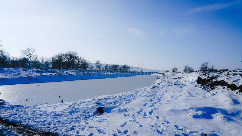Un fiume congelato nella cattività vicino al freddo Neve e cielo blu con le nubi ed il bastone Gradisco camminare su un fiume con immagini stock