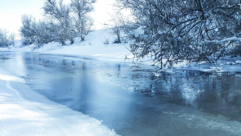 Un fiume congelato nella cattività vicino al freddo Neve e cielo blu con le nubi ed il bastone Gradisco camminare su un fiume con fotografia stock libera da diritti