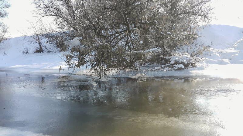 Un fiume congelato nella cattività vicino al freddo Neve e cielo blu con le nubi ed il bastone Gradisco camminare su un fiume con fotografia stock