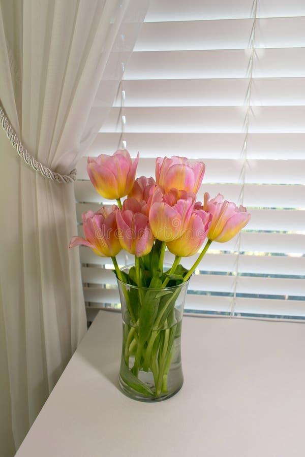 Un florero de tulipanes rosados delante de una ventana con las persianas y curta imagen de archivo