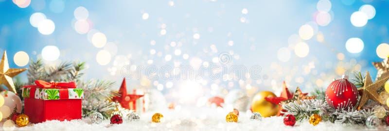 Un fond d'hiver de Noël avec boîte cadeau, baubles de Noël et branches de sapin sur neige photos libres de droits