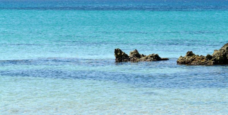 Un fondo azul de la naturaleza del mar y de las rocas foto de archivo