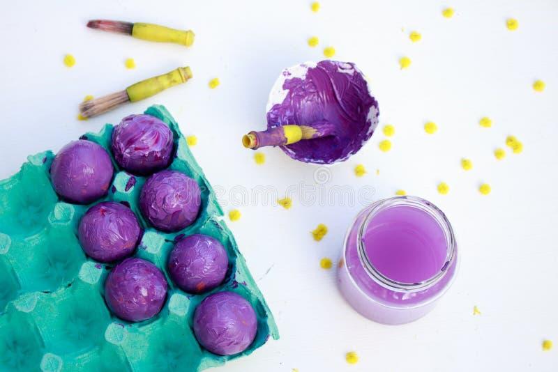 Un fondo bianco con gli strumenti per la tintura delle uova di Pasqua Attività di Pasqua dei bambini Uova colorate immagine stock libera da diritti