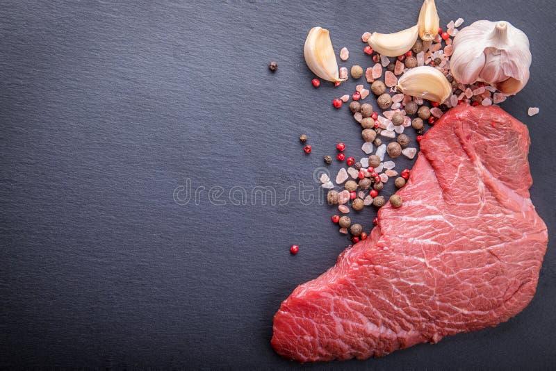 Un fondo con un pedazo crudo de carne de vaca y de verduras, un proceso imagen de archivo