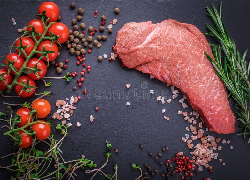 Un fondo con un pedazo crudo de carne de vaca y de verduras, un proceso imágenes de archivo libres de regalías