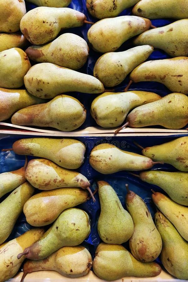 Un fondo de peras en un caj?n Fondo amarillo y verde fresco de las peras fotografía de archivo libre de regalías