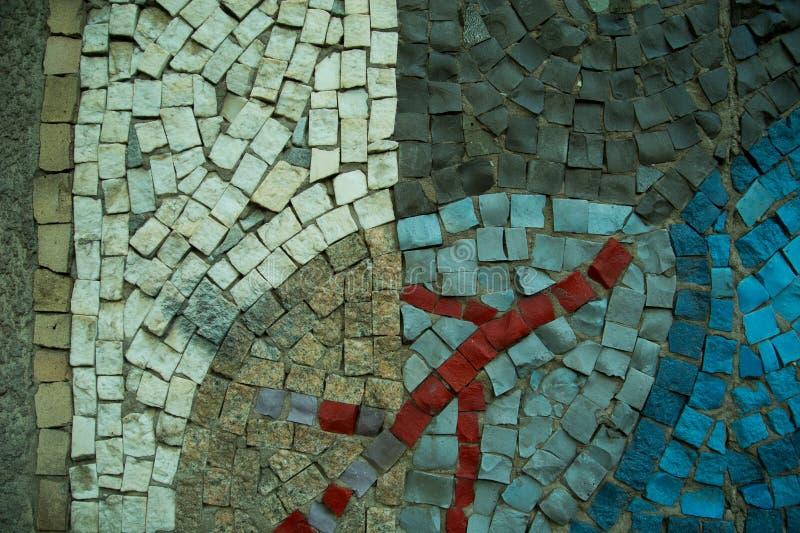 Un fondo decorativo coloreado de la piedra de pavimentación con el estampado de flores foto de archivo