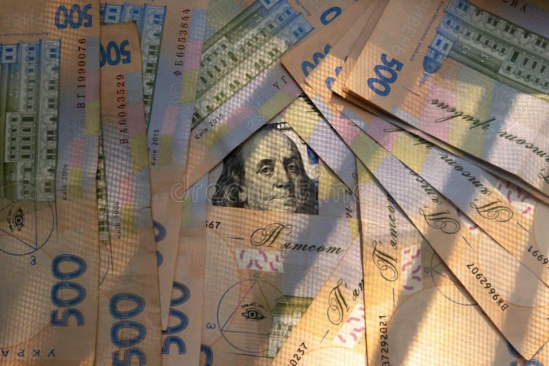 Un fondo di cinquecento banconote ucraine di hryvnia e di singola banconota di cento dollari fotografie stock libere da diritti