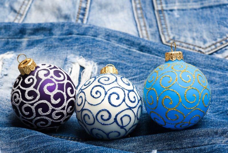 Un fondo di tre di natale delle palle della decorazione pantaloni del denim Concetto di vacanza invernale Decori l'albero di Nata fotografia stock