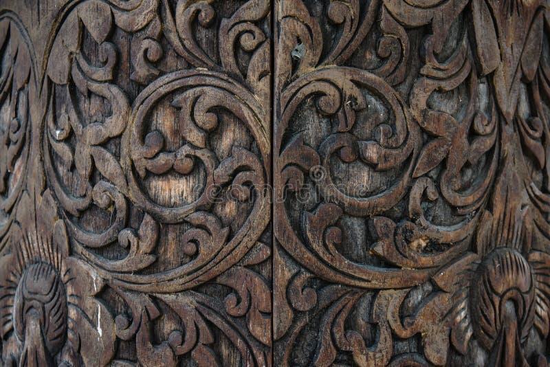 Un fondo scolpito estratto di legno di marrone scuro fotografie stock