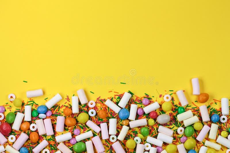 Un fondo variopinto con le caramelle e le caramelle gommosa e molle su un fondo giallo immagine stock libera da diritti