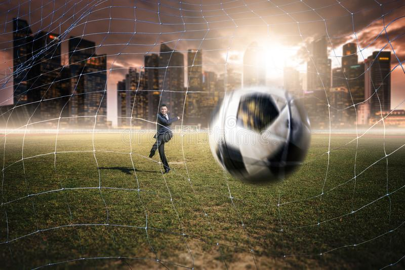 Un football asiatique de jeu d'homme d'affaires photographie stock