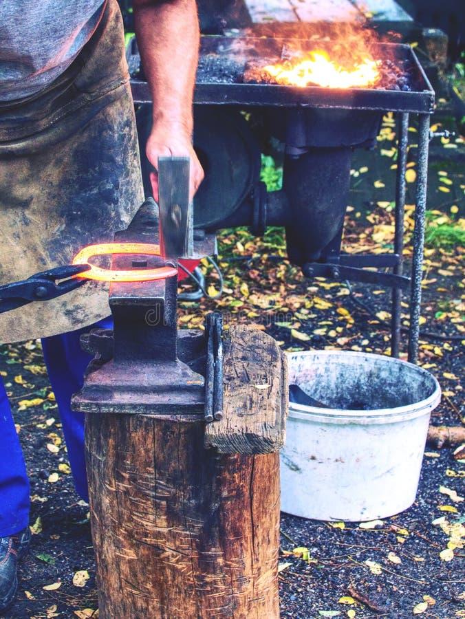 Un forgeron habile en train de frapper un fer à cheval rouge sur l'enclume photos libres de droits