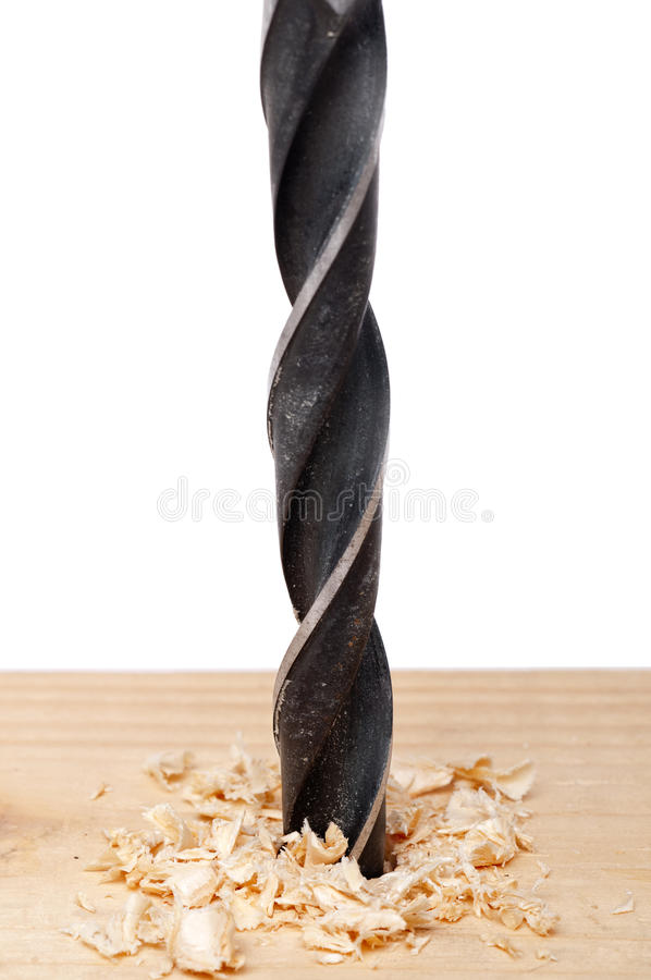 Un foro che è alesato nel legno con un bit di trivello fotografia stock