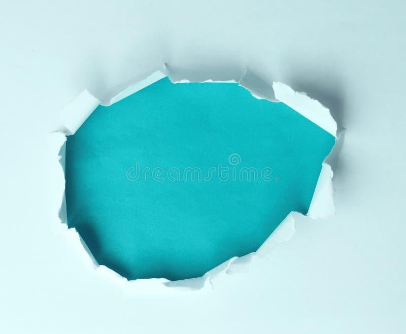 Un foro lacerato la carta su un fondo blu per il vostro testo di pubblicità fotografia stock libera da diritti