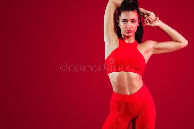 Un forte ballerino della donna e atletico, posante sul fondo rosso che dura nella motivazione degli abiti sportivi, di forma fisi fotografia stock