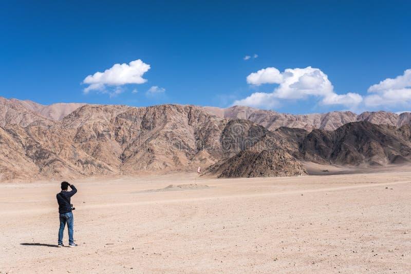 Un fotógrafo del hombre que toma una foto del paisaje de montañas y del cielo azul en Ladakh fotos de archivo libres de regalías