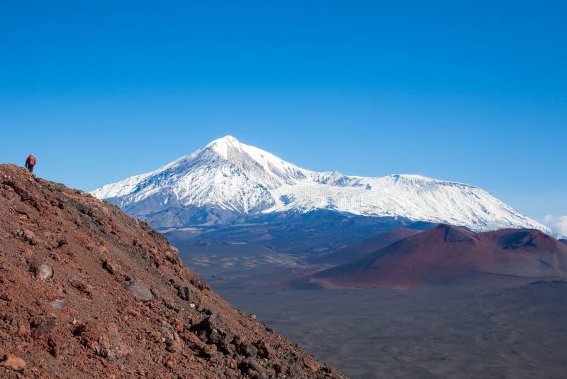 Un fotografo turistico alla cima della montagna prende le immagini del paesaggio dei vulcani kamchatka fotografia stock